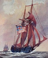 A two-masted wooden sailing ship is shown in full sail on the sea.  It is flying the flag of the United Colonies: thirteen red and white stripes, with a British Union Jack in the upper left quadrant.  Another ship is visible in the distance.