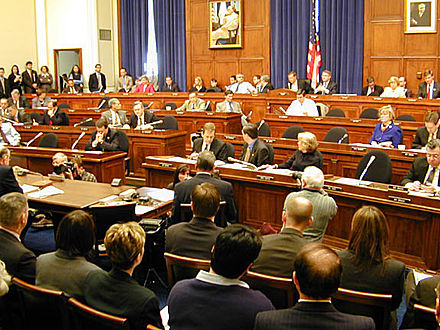 The House Financial Services committee meets. Committee members sit in the tiers of raised chairs, while those testifying and audience members sit below. US House Committee.jpg