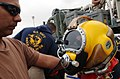 US Navy 030311-N-5362A-004 Equipment Operator 2nd Class Chris Amescua receives assistance from his dive supervisor.jpg