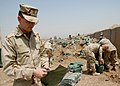 US Navy 070425-N-3560G-015 Navy Chaplain, Lt. Peter Ott, assigned to Naval Mobile Construction Battalion (NMCB) 4 lends a hand filling sandbags for various construction projects.jpg