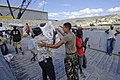 US Navy 080923-N-9620B-004 Boatswain's Mate 3rd Class Christian Farfan, embarked aboard the amphibious assault ship USS Kearsarge (LHD 3), helps a Haitian relief worker unload food and water to aid those affected by recent hurr.jpg