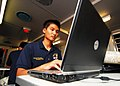 US Navy 100830-N-4044H-028 Kevin To, a University of California, San Diego Pre-Dental Society volunteer embarked aboard the Royal Australian Navy landing ship heavy HMAS Tobruk (L50), works on his dental school application.jpg