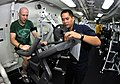 US Navy 101024-N-7103C-079 Lt. j.g. Neal Soladay, left, from Columbia, S.C., finishes his 20-minute cycle on an exercise bicycle during an indoor t.jpg