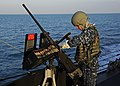 US Navy 111125-N-VH839-001 Gunner's Mate 2nd Class Jeremy Bennett mans a mounted .50-caliber machine gun aboard the Arleigh Burke-class guided-miss.jpg