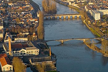 """Vista aérea de la ciudad de Châtellerault y del curso del río Vienne. En la parte inferior, el """"puente de Camille de Hogues"""" diseñado y construido por François Hennebique"""