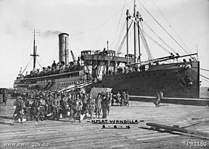 A crowd of diggers in slouch hats pose in front of a ship docked at the wharf.