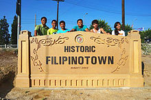 Photograph of a sign located in Los Angeles with people standing behind it that reads Historic Filipinotown