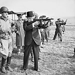 Winston Churchill fires a Thompson submachine gun alongside the Allied Supreme Commander, General Dwight D Eisenhower, during an inspection of US invasion forces, March 1944. H36960.jpg