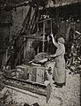 Woman operating boring machine; boring wooden reels for winding barbed wire (5711501148).jpg
