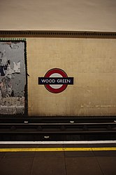 WoodGreen - Roundel and advertising on westbound platform before (4571454278).jpg