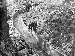 Hydraulic mining - A man leans over a wooden sluice. Rocks line the outside of the wood boards that create the sluice.