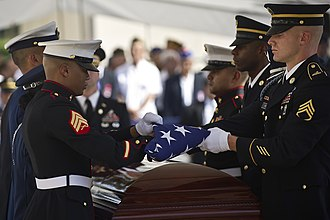 Daniel Inouye - A joint military honor guard folds a US flag over Inouye's casket at the National Memorial Cemetery.