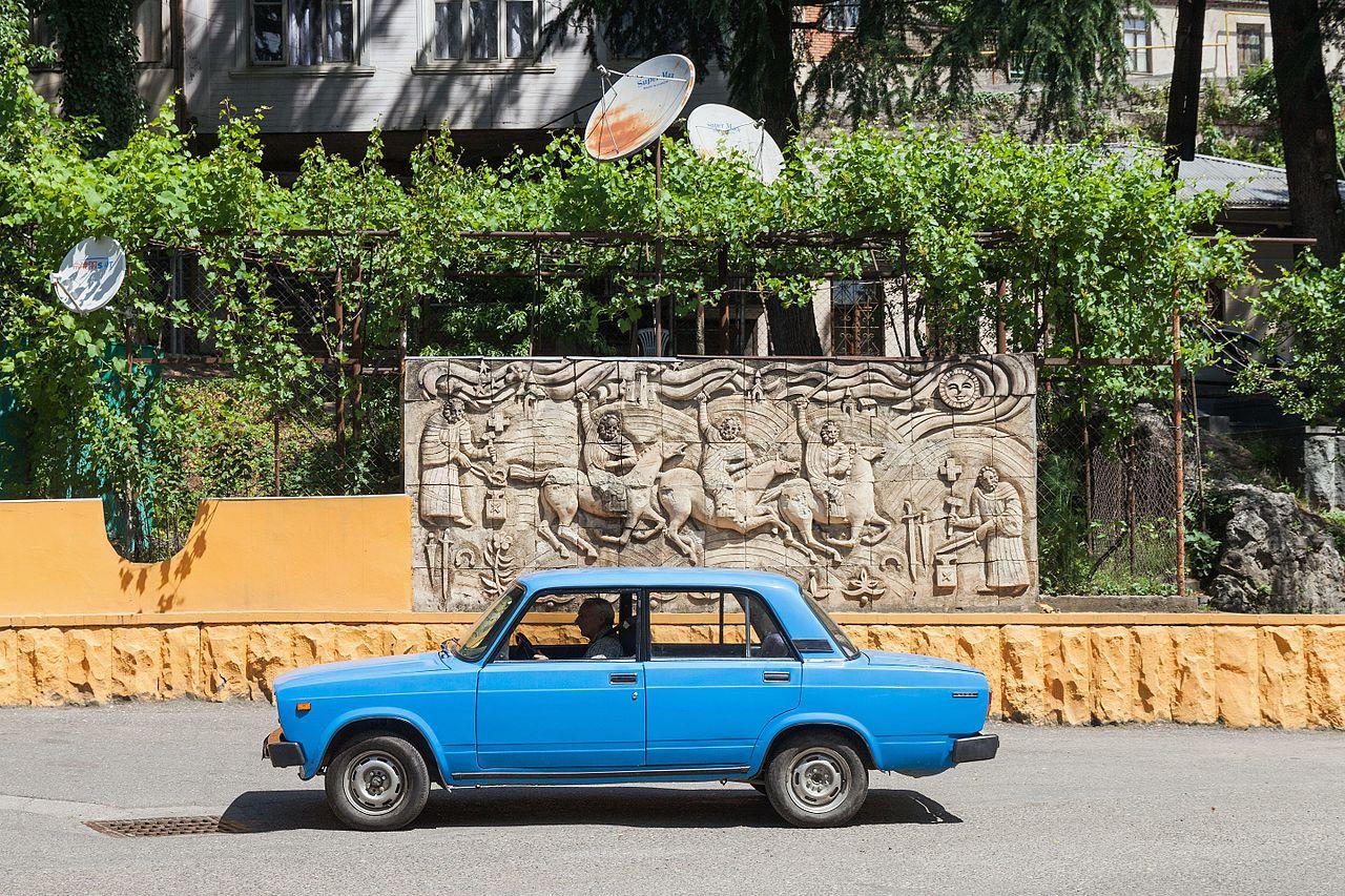 2014 Kutaisi, Płaskorzeźba obok stacji benzynowej i samochód Łada.jpg