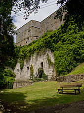 exterior shot of forbidding, ivy-covered citadel wall