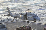 A U.S. Navy MH-60S Seahawk helicopter assigned to Helicopter Sea Combat Squadron (HSC) 22 lifts cargo from the flight deck of the fast combat support ship USNS Arctic (T-AOE 8) during a replenishment at sea with 140101-N-CC806-049.jpg