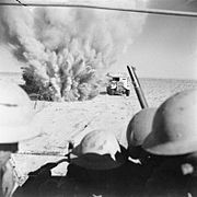 A mine explodes close to a British truck as it carries infantry through enemy minefields and wire to the new front lines