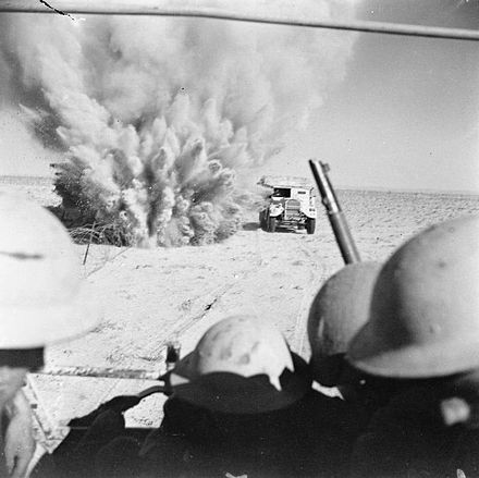 War in the desert: Battle of El Alamein, 1942 A mine explodes close to a British truck as it carries infantry through enemy minefields and wire to the new front lines.jpg