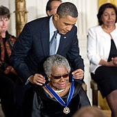 An elderly African-American woman, seated, smiling broadly, and dressed in black, being given an award by an African-American man in his fifties, wearing a blue tie and leaning over from behind her.