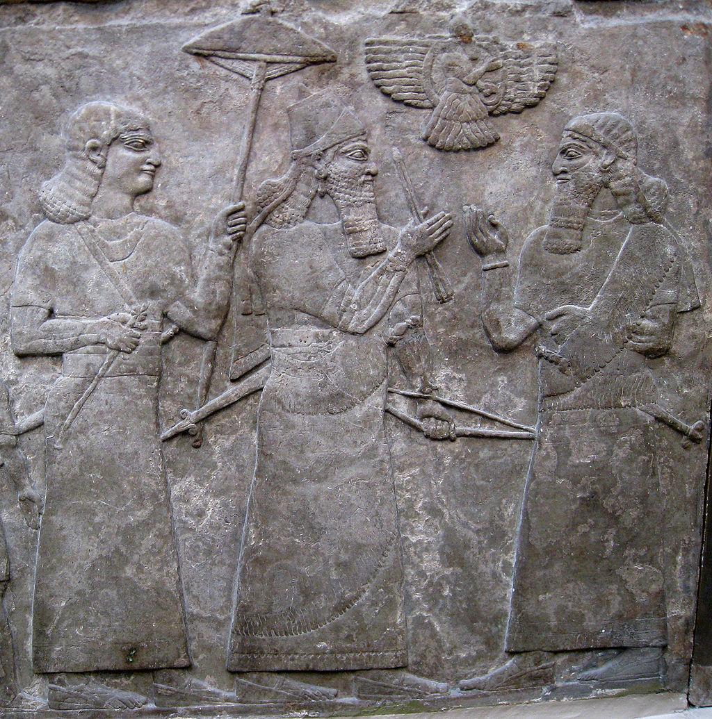 آشورناصیرپال دوم در حال ملاقات با یک مقام عالیرتبه به هنگام سان دیدن از سربازان و اسیران جنگی. در پشت وی نگهبانی با چتر آفتابی ایستاده است. پادشاه توسط یک ایزد بالدار محافظت میشود. او کمانی را با دو تیر بیرون کشیده شده در دست دارد که نماد پیروزی وی در جنگ است، از قصر شمالغربی در نیمرود، حدود ۸۶۵-۸۶۰ پ. م. ، موزه بریتانیا