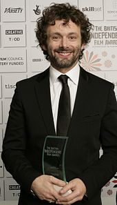 Michael Sheen, a caucasian male in his late-30s with dark shaggy curly hair. He wears a black suit and white shirt with a black tie. He smiles and holds a glass award with both his hands.