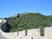 The Great Wall of China, surrounded by trees, against a blue sky