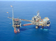 An oil platform constructed in two main parts sits in a calm blue sea. The larger section at right has a helideck, the smaller at left is flaring gas from two stacks.