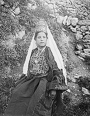 A woman in Bethlehem. Her headdress and short jacket are typical of the Bethlehem area.