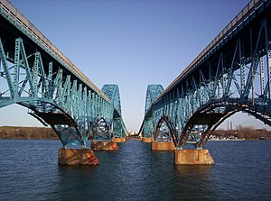 Twin spans of the South Grand Island Bridge, which cross the Niagara River in five sky-blue steel arches. The central arch is above the roadway permitting passage of large freight ships.