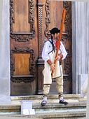 A man playing the fujara instrument in front of a large wooden door