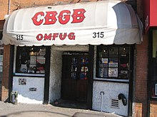 "The front of the music club CBGB is shown. An awning has the letters CBGB painted on it. Below the name are the letters ""OMFUG""."