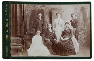 A photograph of a wedding party probably from the late 1870s to 1880s.(Note the black or dark colored wedding dress which was common during the early to mid 19th century.)