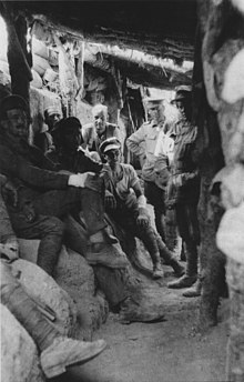 Soldiers sitting in a trench beneath a log roof