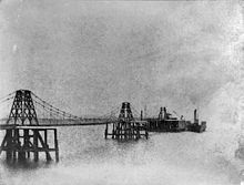 A slightly indistinct black-and-white image of a suspension pier. There is a paddle-steamer docked to the pier at the right. Another one is barely visible through the pier on the left. There is a small building on the platform at the end of the pier, and what may be a crane.