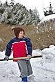 Child using a snow shovel to remove snow 01.jpg