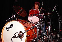 Chris Layton playing a drum kit. He has dark hair and is looking upwards.