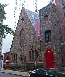 "A brown stone triangular building with a square tower at the right on a city street. Its windows have pointed arches and there are similarly shaped red doors on either side. A large purple banner hanging from it has the word ""Resurrection"" on it"