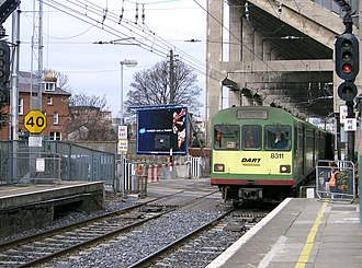 Ballsbridge - A DART train passes under the Lansdowne Road Rugby Stadium (since demolished and replaced by Aviva Stadium) and over the level crossing as it enters Lansdowne Road railway station.