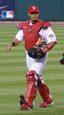 A baseball player walks in from the bullpen in his catcher's gear.