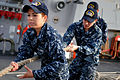 Defense.gov News Photo 110309-N-9818V-229 - Seaman Erika Berry and Seaman Robert Toohey heave a line during sea and anchor detail aboard the guided-missile destroyer USS Decatur DDG 73 near.jpg