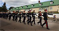 Soldiers marching down a street in black uniforms