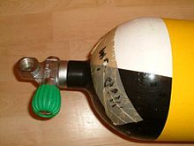 The shoulder of a scuba cylinder and a pillar valve are shown. The cylinder is yellow with black and white quartered shoulder, there is a tape stuck to the shoulder indicating maximum operating depth and the cylinder valve has a DIN connection opening directly above the neck thread, perpendicular to the cylinder axis, and a rubber knob on an orthogonal valve spindle in the right handed configuration.