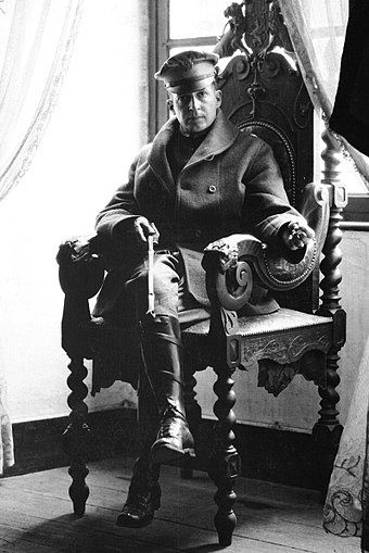 Brigadier General MacArthur holding a riding crop at a French chateau, September 1918 Douglas MacArthur, Army photo portrait seated, France 1918.JPEG