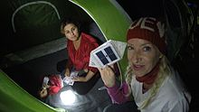 Full-time volunteer, Dr. Alison Thompson is handing a Syrian family a solar lantern called SolarPuff to light their dark tent at the Idomeni refugee camp in Greece. 2015