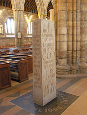 a cuboid-shaped standing stone with words engraved on its sides and on the floor where it stands.