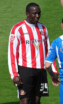 Dwight Yorke wearing a long-sleeved red-and-white-striped football jersey and white shorts with a number 34 on the left leg.