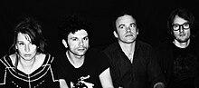 Photographie en noir et blanc de quatre musiciens.