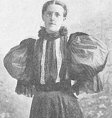 Photograph of a bespectacled woman with her hair pulled away from her face, wearing a frilled high-necked blouse with extremely large puffed sleeves and a striped bodice.
