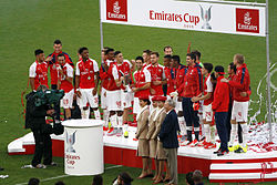 A coloured photograph of the Arsenal squad standing on a podium, celebrating their fourth Emirates Cup win.