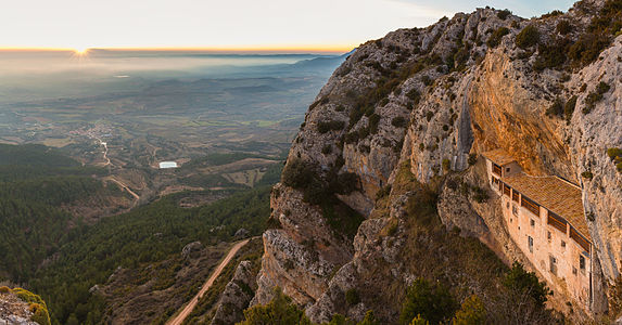 Sunset view of the Ermita de la Virgen de la Peña (Hermitage of the Virgen of the Rock) with the village of Aniés in the front, province of Huesca, Spain. The oldest parts of the sanctuary are romanic and date from the middle edge (13th century). The hermitage is only accesible on foot through a steep path in the forest or caved in the mountain.