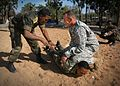 Ethiopian National Defense Lt. Tadele Abebe watches a demonstration by U.S. Army Staff Sgt. Robert Conley, from Assaria, Kan., on how to handle and handcuff a suspect.jpg